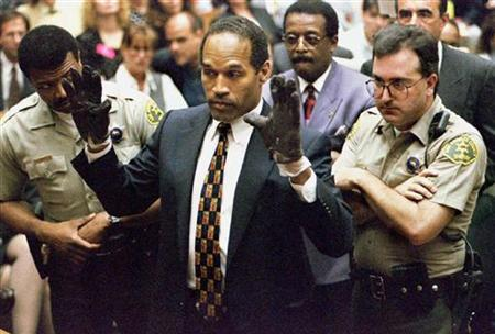 O.J. Simpson holds up his hands to the jury wearing the infamous gloves found at the crime scene and his home in this June 15, 1995 file photo. REUTERS/Sam Mircovich/Files
